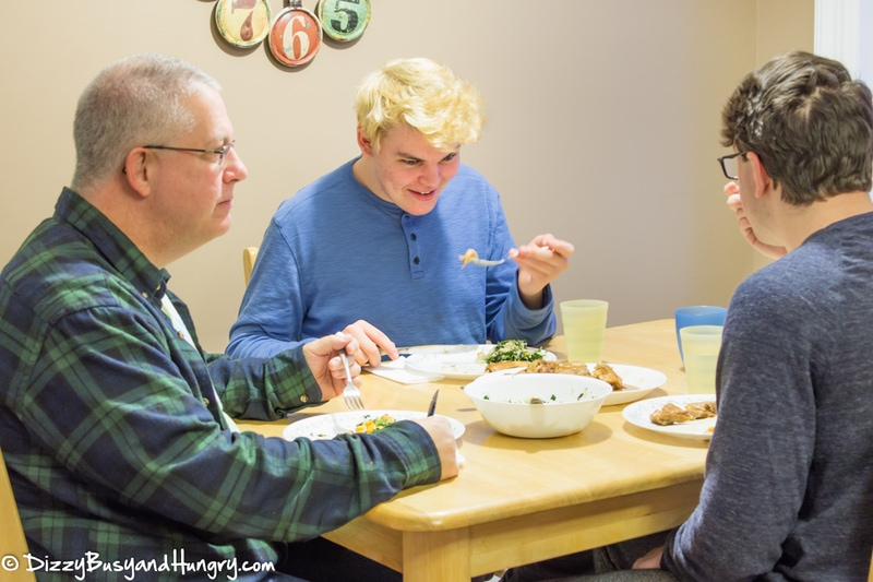 Side view of three men sitting at the dinner table eating a meal.