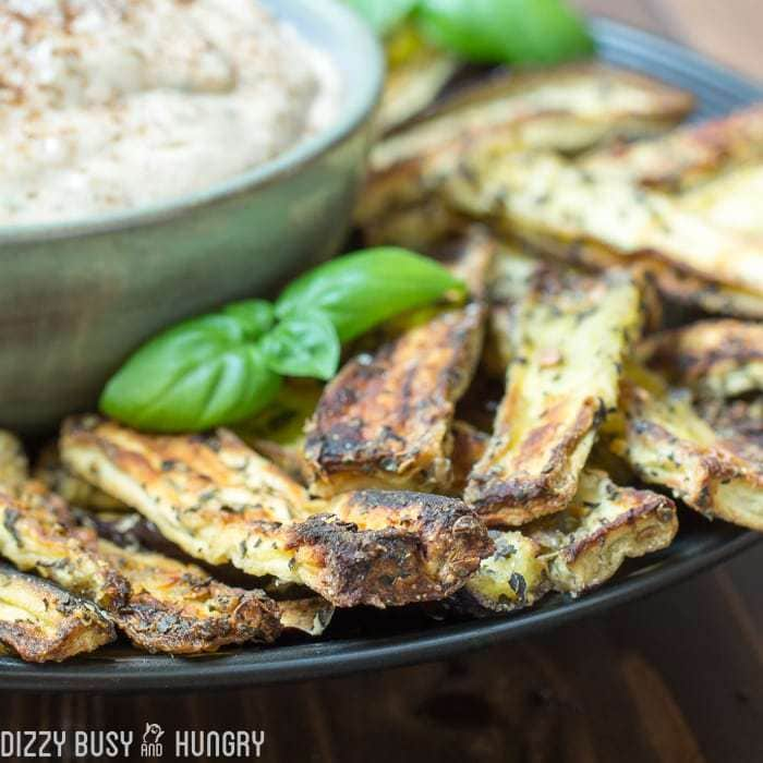 Side shot of eggplant fries surrounding a bowl of basil dipping sauce garnished with herbs.
