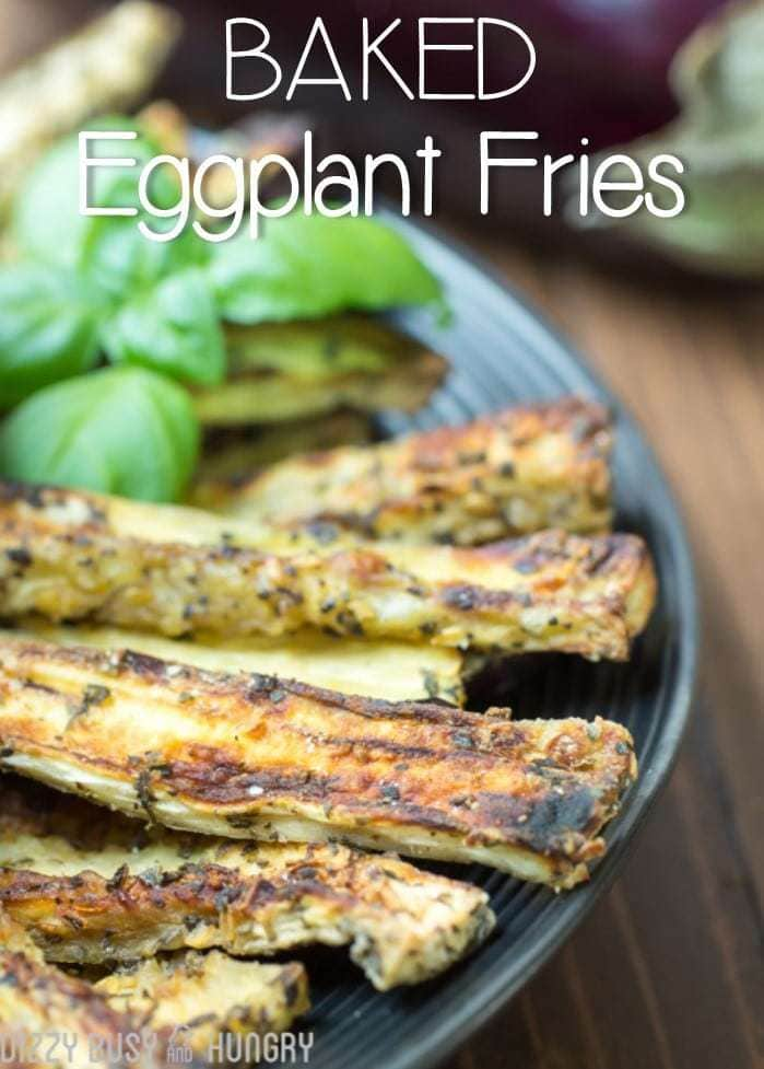 Close up shot of eggplant fries garnished with herbs on a black plate.