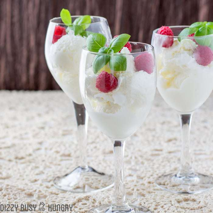 Side shot of moscato ice cream in three wine glasses garnished with mint and raspberries.