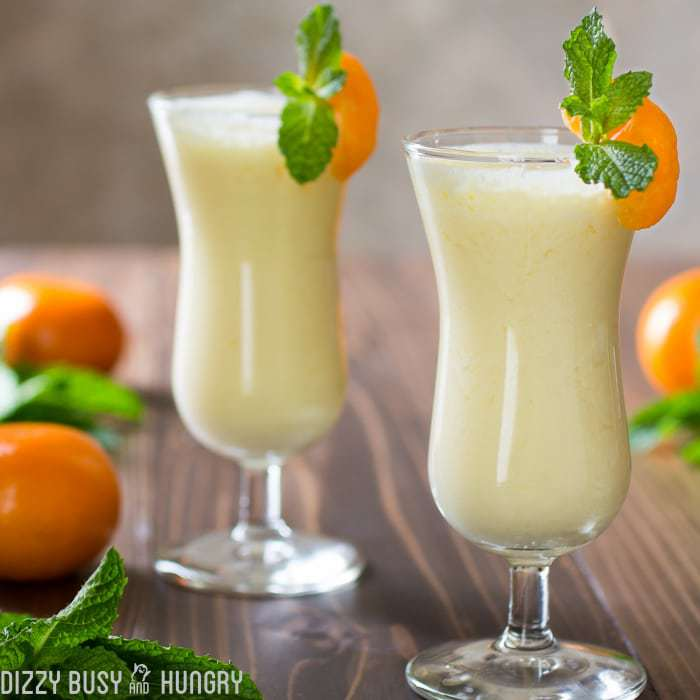 Side shot of pineapple orange smoothie in two wine glasses garnished with orange and mint.