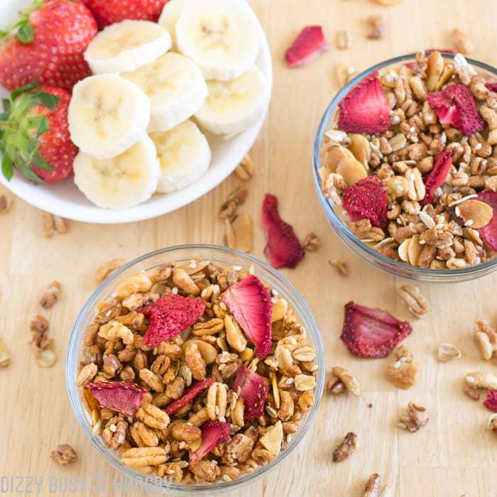 Strawberry granola in two clear bowls sprinkled with dried strawberries with sliced banana and strawberries on the side.
