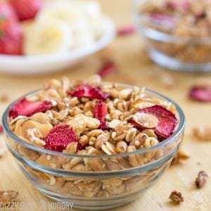 Close up shot of strawberry granola in a clear owl with sliced bananas and strawberries in the background.