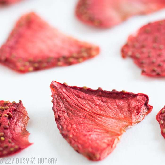 Close up shot of dried strawberries on a white surface.