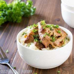 Side shot of crock pot chicken thighs in a white bowl on a wooden surface with herbs and a fork in the background.
