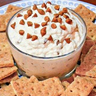 Close up shot of cinnamon cannoli dip in a clear bowl surrounded by graham crackers on a blue plate.