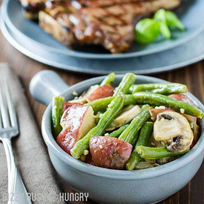 Side view of French onion green beans in a blue bowl with a grilled porterhouse steak on a blue plate in the background.