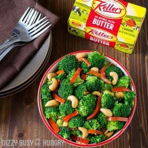 Red pepper garlic butter broccoli in a red bowl with more plates, silverware, and Keller's butter in the background.
