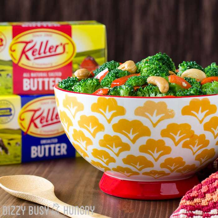 Red pepper garlic butter broccoli in a red and orange bowl with a wooden spoon and Keller\'s butter in the background.