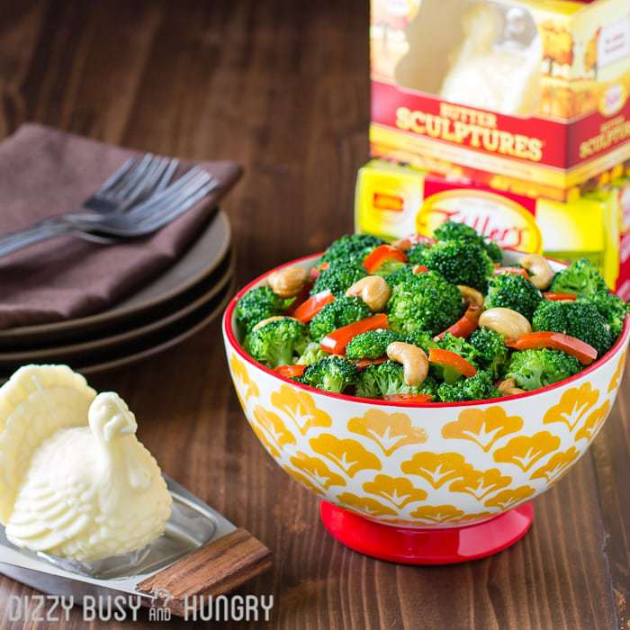Red pepper garlic butter broccoli in a red bowl with more plates, silverware, and Keller\'s butter in the background.