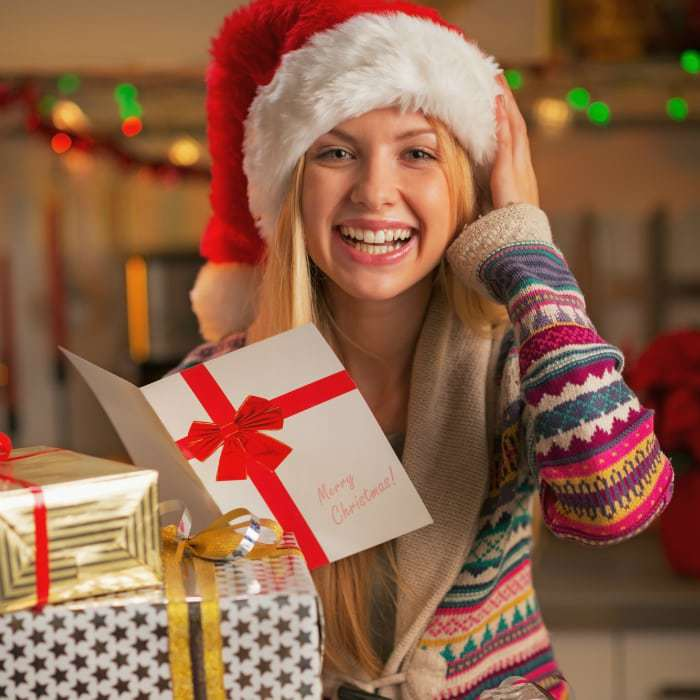 Side view of a woman wearing a Santa hat holding up a Christmas card and smiling.