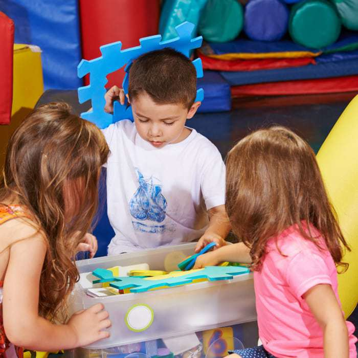 Side view of three toddlers playing with large puzzle pieces.