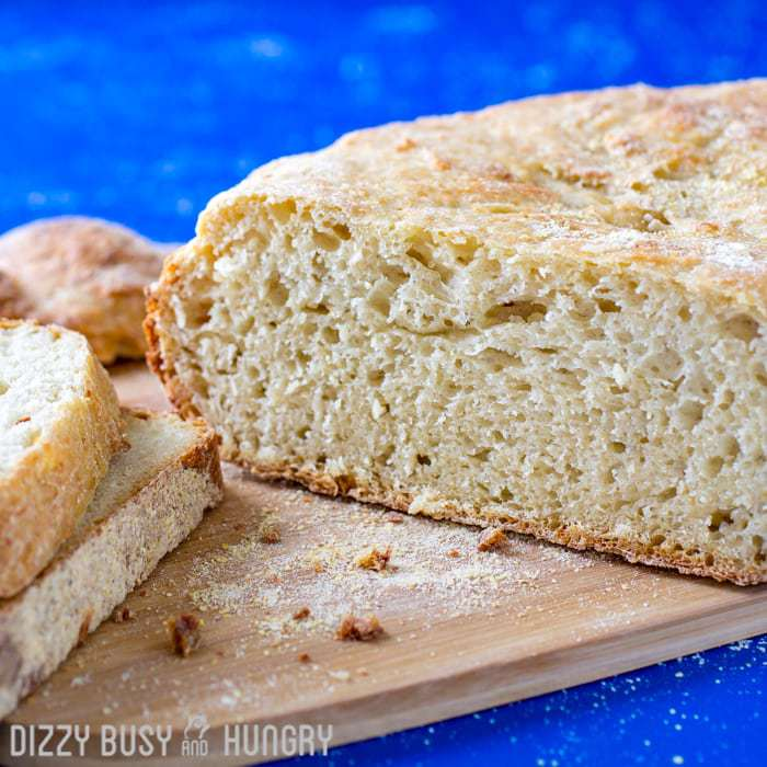 Close up shot of whole garlic parmesan bread with slices on the side on a wooden cutting board with a blue background.
