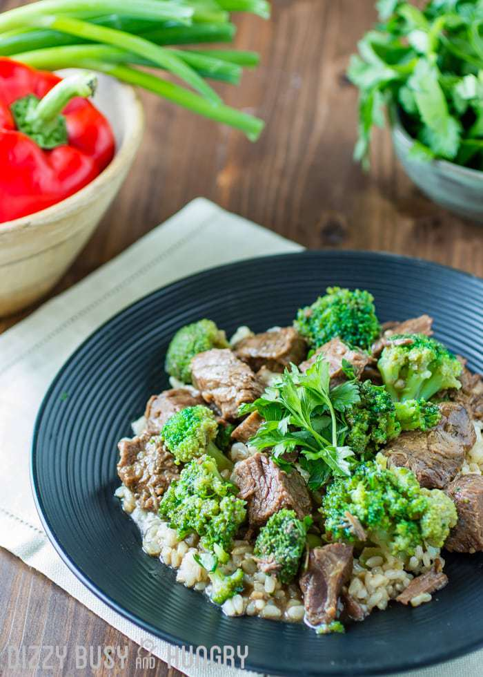 Crock pot beef and broccoli sprinkled with herbs on a black plate with red peppers and greens in the background.