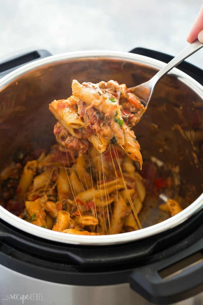 Close up shot of a fork showing instant pot baked ziti with more in the instant pot in the background.