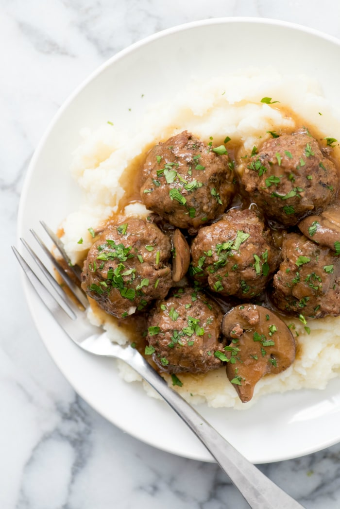 Overhead shot of Swedish meatballs on mashed potatoes on a white plate with a fork on the side.