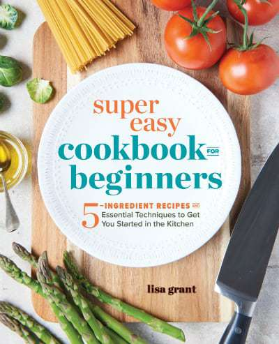 """Close up shot of a sign that says \""""Super easy cookbook for beginners\"""" on a white plate with vegetables surrounding it."""