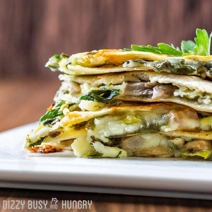 Side view of multiple spinach mushroom quesadillas stacked on a white plate with herbs in the background.