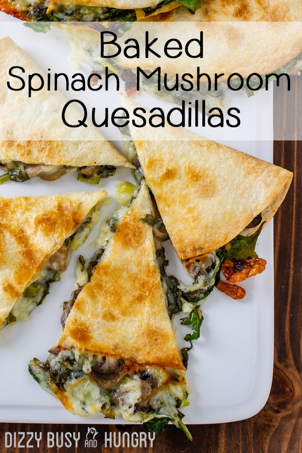 Overhead shot of baked spinach mushroom quesadillas sliced into pieces on a white plate.
