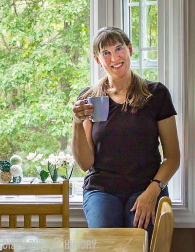 Side view of a woman sitting on a bench holding a cup of coffee in front of a large window.