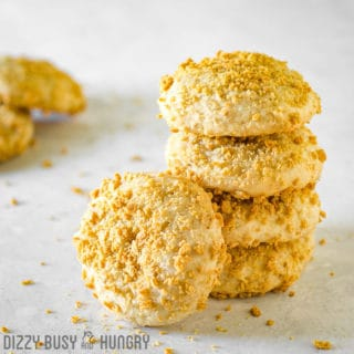 Side view of multiple banana graham cookies stacked on a white surface.