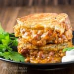 chili cheese grilled sandwich halves stacked on a brown plate with parsley garnish