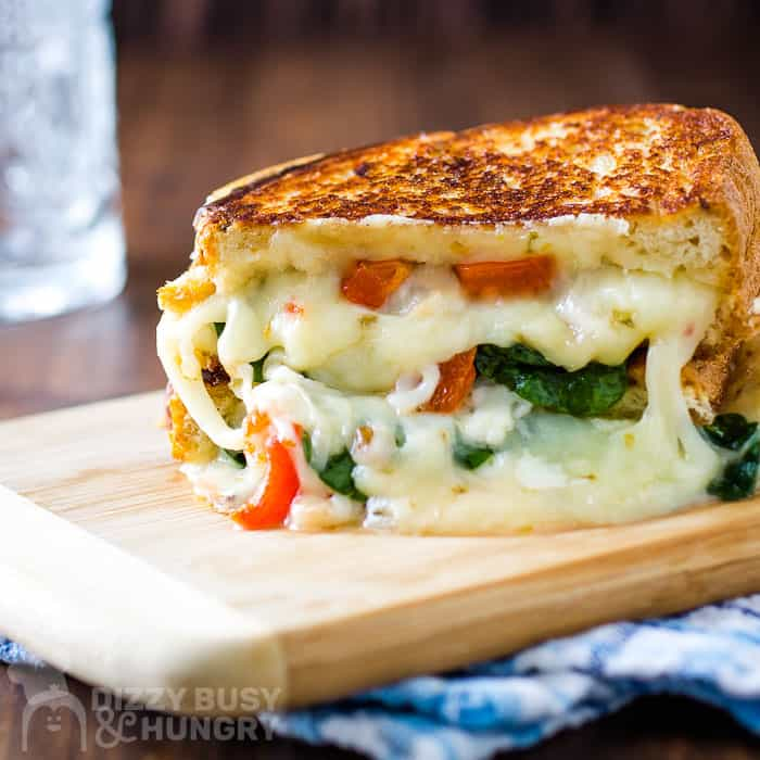 front view of stacked grilled sandwich pieces with red peppers, spinach, and cheese oozing out