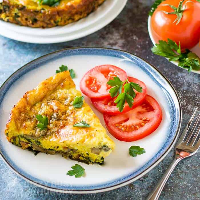 view of baked frittata slice with the whole frittata in the background