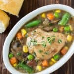 Overhead shot of crock pot Guinness chicken stew in a white oval bowl with sliced bread on the side.