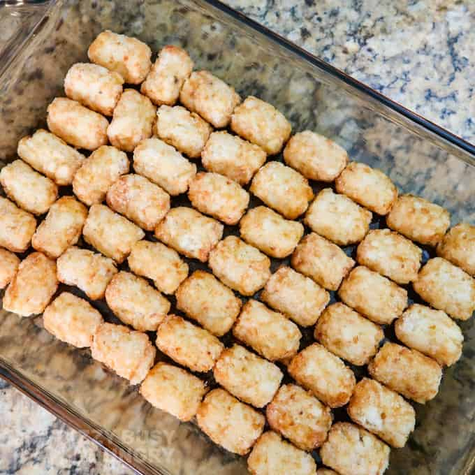 Overhead view of the frozen tater tots lining the bottom of the 11x7 casserole dish