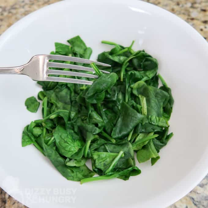 Overhead view of using a fork to separate the wilted spinach in a white bowl