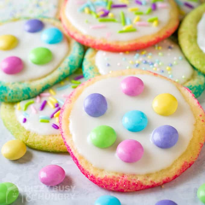 Easter sugar cookies with colored edges and white glaze with pastel chocolate candies and sprinkles.