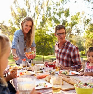Busy families connect with kids and parents enjoying a meal at a picnic table