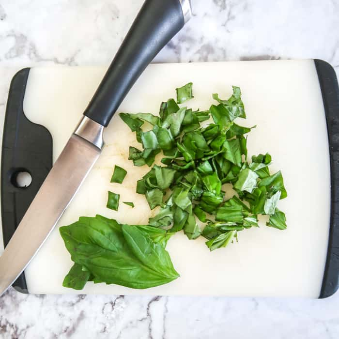Process shot of the chopped basil and a knife on a cutting board.