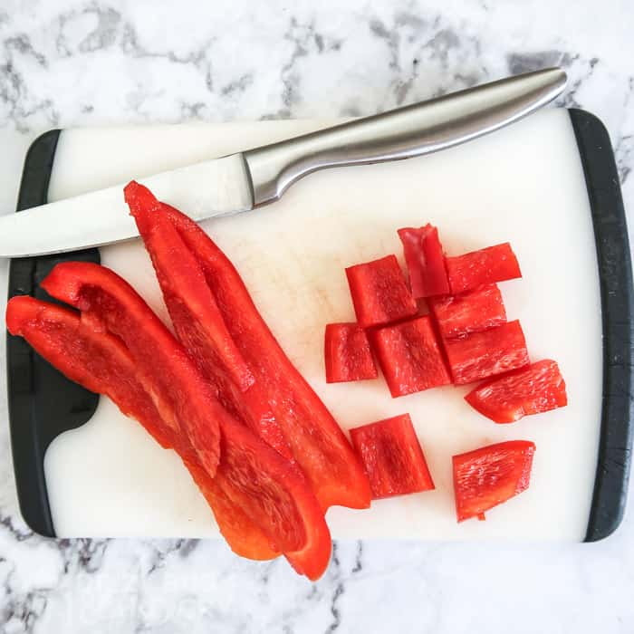 Process shot of the red bell pepper chopped into chunks for the fruit and vegetable salad.