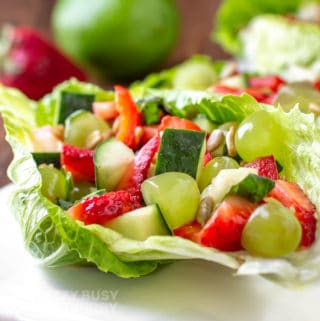 Close side view of finished veggie salad served on a white platter on a crisp green lettuce leaf.