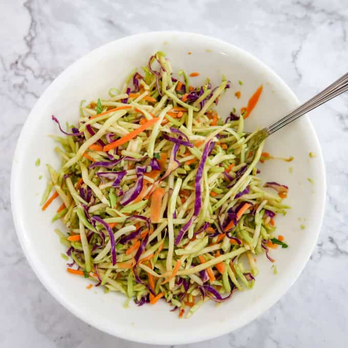 Overhead view of colorful broccoli slaw with carrot and red cabbage shreds in a medium white bowl.