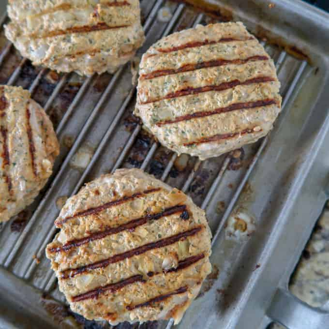 Overhead view of delicious looking burgers cooking on a grill top with attractive grill marks