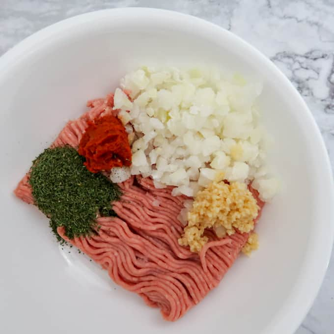 Overhead view of burger patty ingredients in a white bowl ready to be mixed together.
