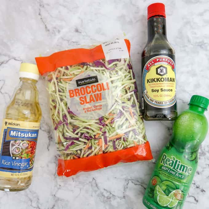 Overhead view of rice vinegar, broccoli slaw, soy sauce, and lime juice.