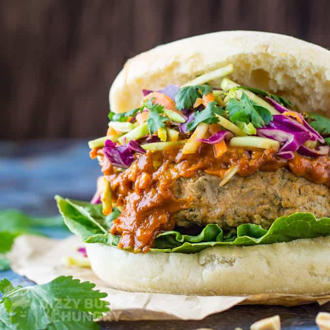 Front angle view of Thai turkey burger nestled on a bed of lettuce and piled high with peanut sauce and Asian-style slaw.