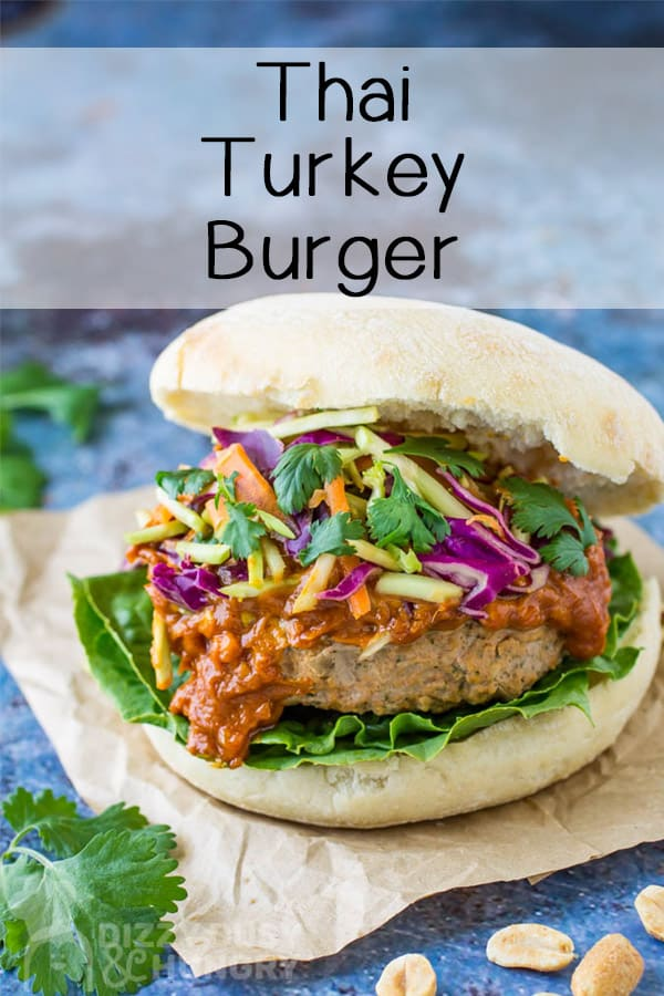 Overhead angle view of Thai turkey burger on crumpled brown paper with cilantro garnish