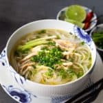 front view of vietnamese Pho Soup with scallion garnish. Soup in Asian bowl and plate