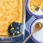 Overhead view of cornbread casserole dish with some of it spooned onto a plate with a wooden spoon.