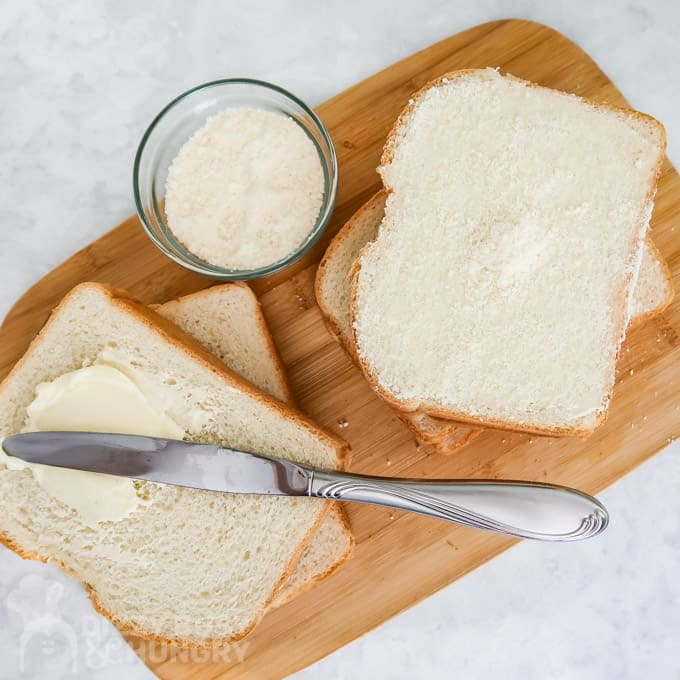 Overhead view of slices of bread with butter and one with the Parmesan cheese coating the butter.