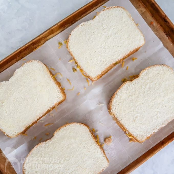Overhead view of 4 Parmesan and butter coated sandwiches on a baking sheet ready for the oven