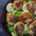 Top view of crispy cooked chicken with lime wedges and cilantro for garnish - Cheap Chicken Recipes