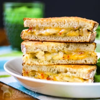 Three halves of a grilled chicken sandwich with cheese stacked on a white plate.