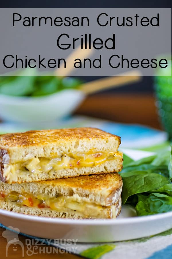 chicken and cheese grilled cheese halves stacked on a plate with a side of fresh spinach leaves