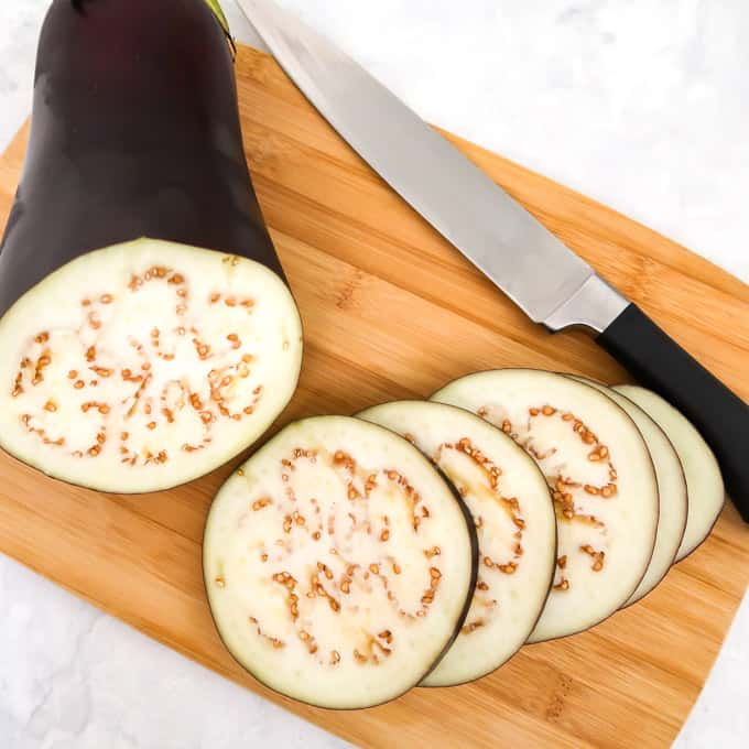Process shot of eggplant cut into five thin rounds on a cutting board with a knife.